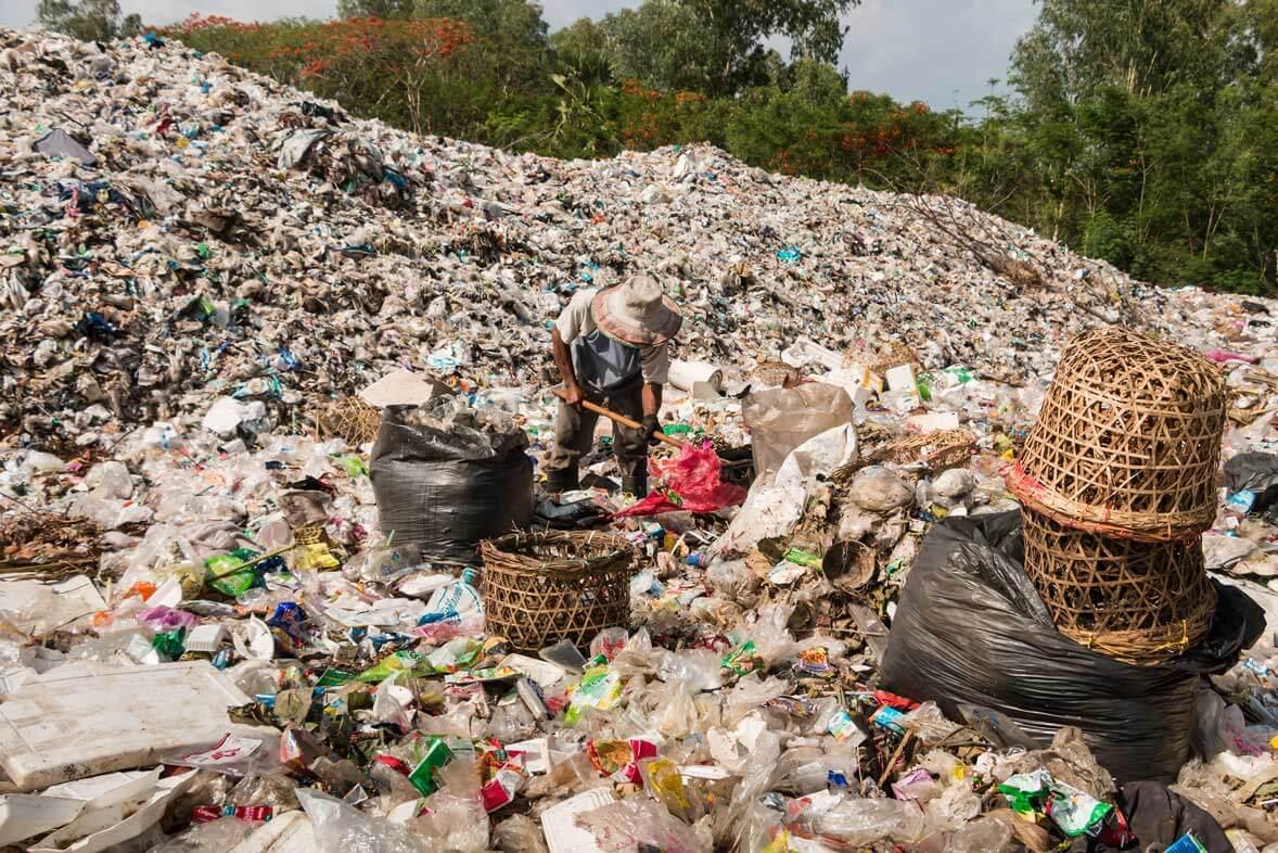 Mann mit Hut auf Müllhalde