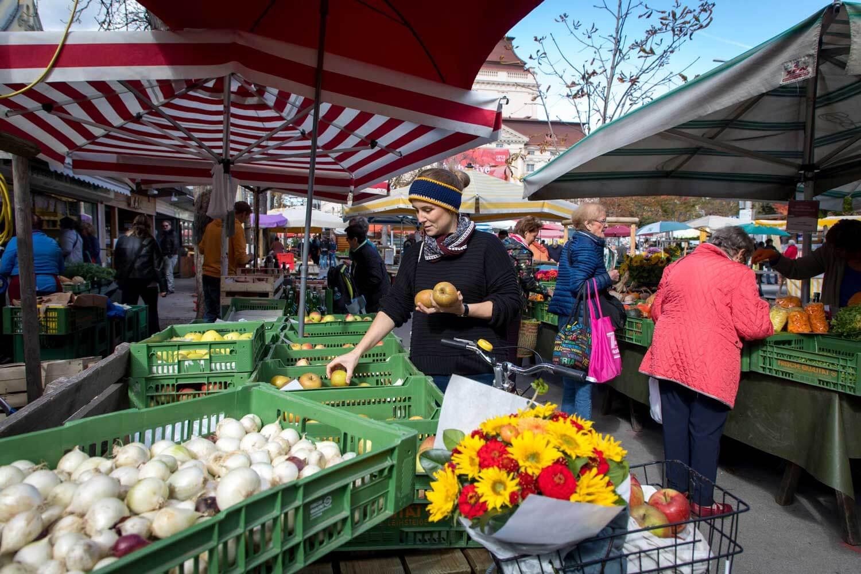 Eine junge Frau kauft am Markt Obst und Gemüse