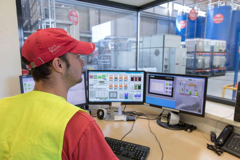 Arbeiter sitzt vor Computer und Glasfenster, davor CP-Anlage